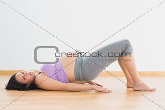 Pregnant brunette lying on floor in bridge pose