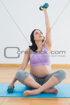 Pregnant brunette sitting on exercise mat lifting hand weight