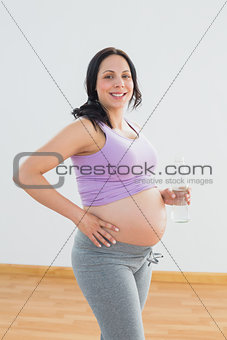 Pregnant woman holding bottle of water smiling at camera