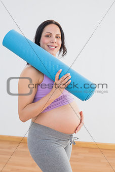 Pregnant woman holding exercise mat smiling at camera