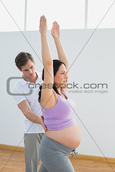 Breathing pregnant woman doing yoga with a personal trainer