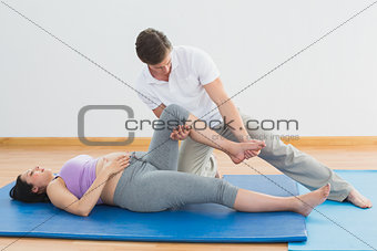Masseur moving pregnant womans leg on blue mat