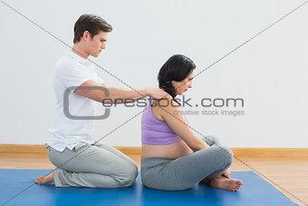 Masseur rubbing pregnant womans shoulders