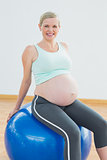 Happy blonde pregnant woman sitting on blue exercise ball
