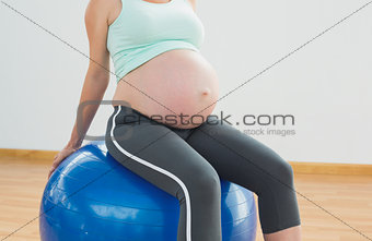 Pregnant woman sitting on blue exercise ball