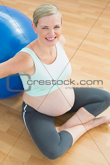 Pregnant woman sitting beside exercise ball smiling up at camera