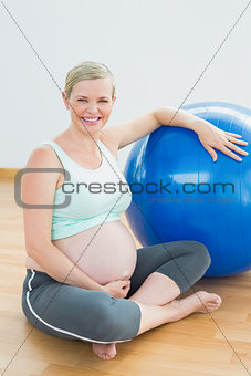 Pregnant woman sitting beside exercise ball smiling at camera