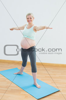 Blonde pregnant woman doing yoga on blue mat smiling at camera
