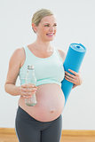 Pregnant woman holding bottle of water and exercise mat