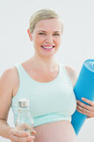 Pregnant woman holding bottle of water and exercise mat smiling at camera