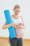 Pregnant woman holding exercise mat sending a text message