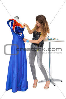 Full length of a female fashion designer and mannequin