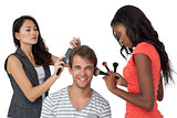 Assistants applying make-up to male model