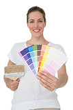Portrait of a woman with paint samples and paintbrush