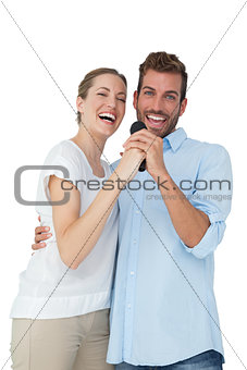 Portrait of cheerful couple singing into microphone