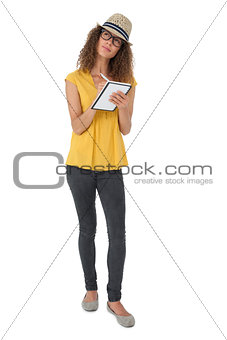 Thoughtful cool young woman writing in notepad