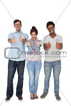 Portrait of three happy friends gesturing thumbs up