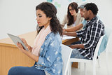 Woman using digital tablet with group in meeting at office