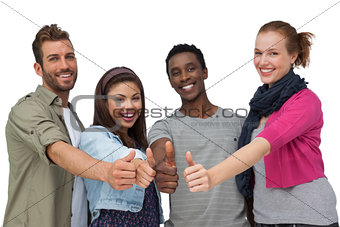 Four happy young friends gesturing thumbs up