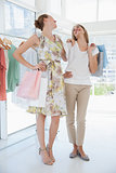 Happy female friends with shopping bags at clothing store