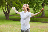 Smiling woman with arms outstretched at park