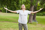 Woman with arms outstretched at park