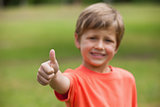 Smiling young boy gesturing thumbs up at park