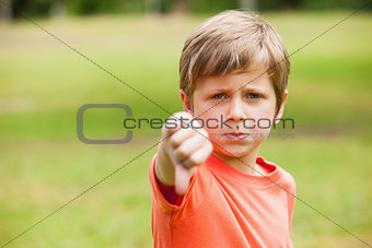 Boy gesturing thumbs down at the park