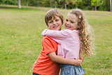 Two smiling kids hugging at park