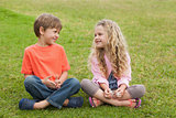 Two smiling kids sitting at park