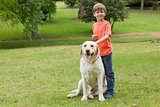 Portrait of a boy with pet dog at park