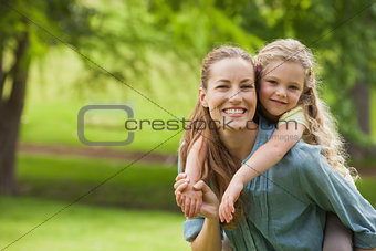 Portrait of woman carrying girl at park