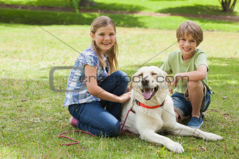 Portrait of kids playing with pet dog at park