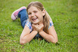 Happy young girl lying on grass at park