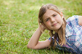 Cute young girl lying on grass at park