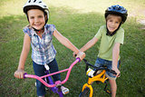 Smiling siblings riding bicycles at park