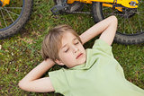 Boy resting besides bicycle at park