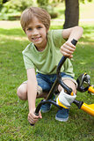 Smiling young boy with bicycle at park