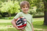 Smiling boy with bicycle helmet at park