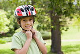 Smiling boy wearing bicycle helmet at park