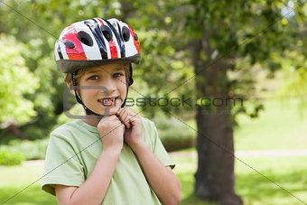 Smiling boy wearing bicycle helmet at park