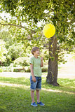 Young boy with yellow balloon at park