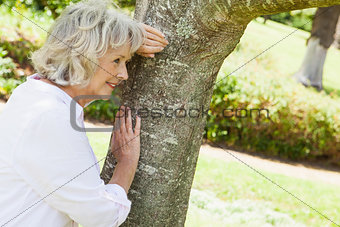 Thoughtful senior woman leaning to tree at park