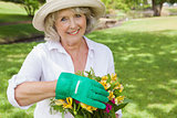 Portrait of a mature woman holding plant at park