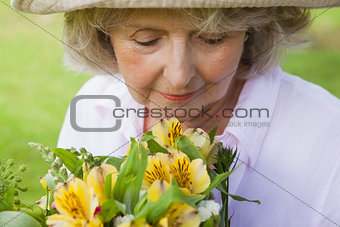Mature woman smelling flowers at park