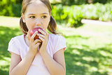 Pretty young girl eating apple in park