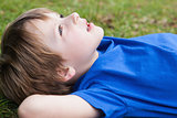 Relaxed young boy lying at park
