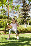 Happy young girl sitting on swing at park