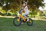 Smiling young girl riding bicycle at park