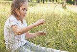 Relaxed young girl sitting in field